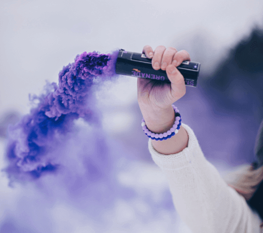 Woman holding purple smoke bomb with two purple silicone beaded bracelets on wrist.