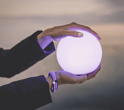 Woman holding glowing purple ball with two purple silicone beaded bracelets on wrist.