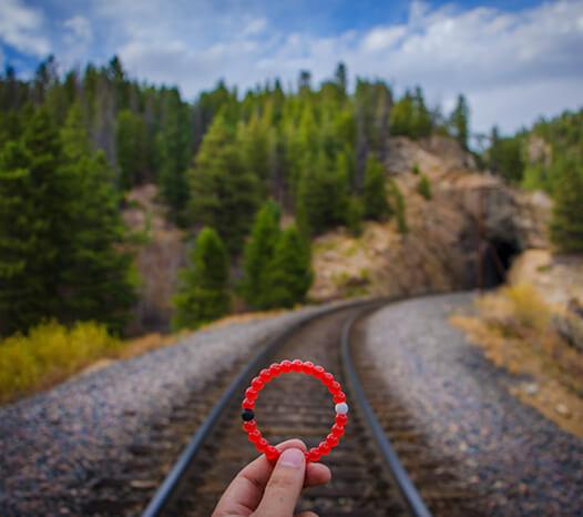 Hand holding red silicone beaded bracelet with train tracks in the background.