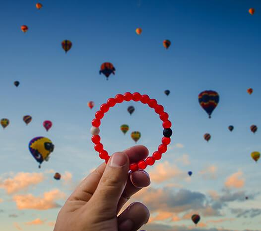 Hand holding red silicone beaded bracelet with hot air balloons in the background.