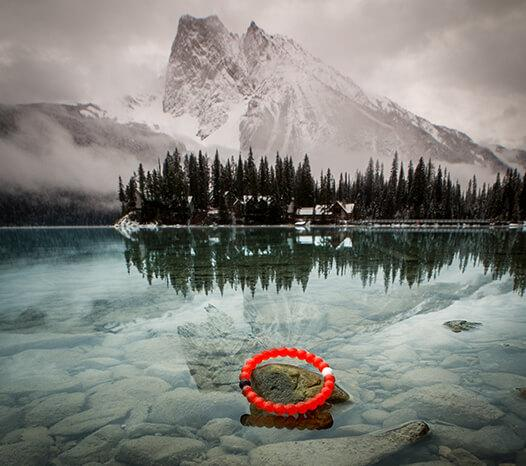 Red silicone beaded bracelet on rock in the water with mountains in the background.