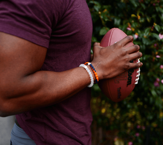 Man holding a football wearing an orange and navy blue silicone beaded bracelet.