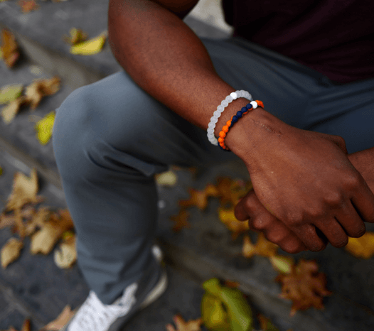 Man holding his wrist wearing an orange and navy blue silicone beaded bracelet.