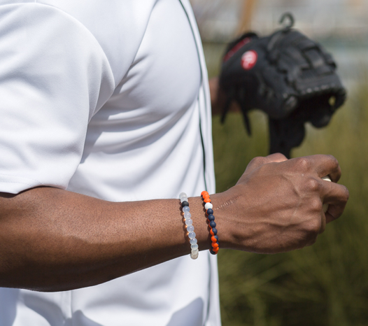 Male wearing orange and navy blue silicone beaded bracelet on wrist while holding a baseball.