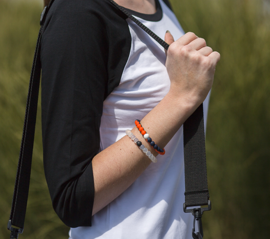 Woman wearing orange and navy blue silicone beaded bracelet on wrist while holding shoulder bag straps.