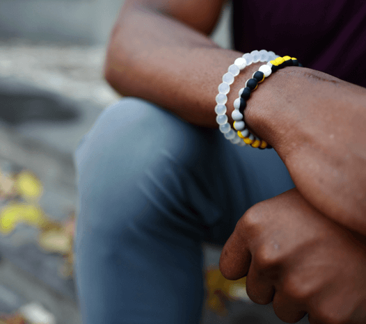 Man holding his wrist wearing a yellow, gray and black silicone beaded bracelet.