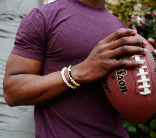 Man holding a football wearing a yellow, gray and black silicone beaded bracelet.