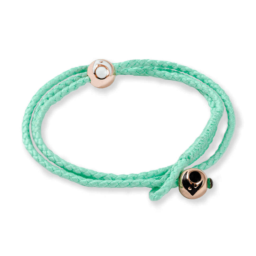 Side angle of mint triple wrap woven bracelet with two rose gold metal beads.