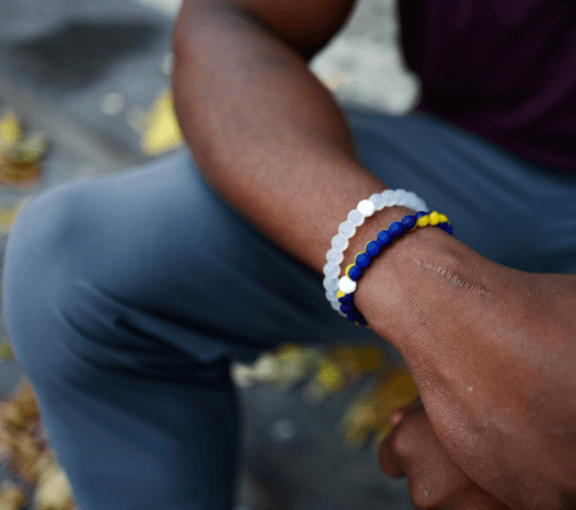 Man sitting wearing a navy blue, yellow and blue silicone beaded bracelet.