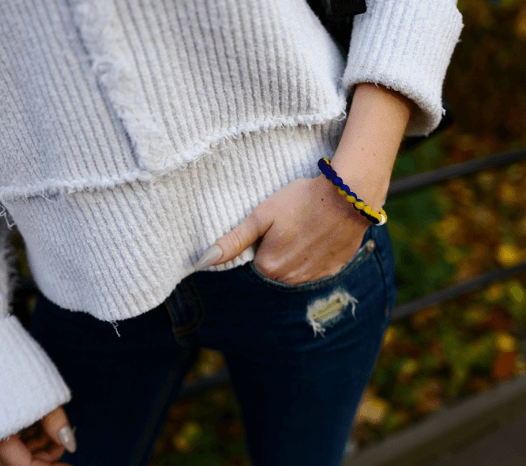 Woman with her hands in her pocket wearing a navy blue, yellow and blue silicone beaded bracelet.