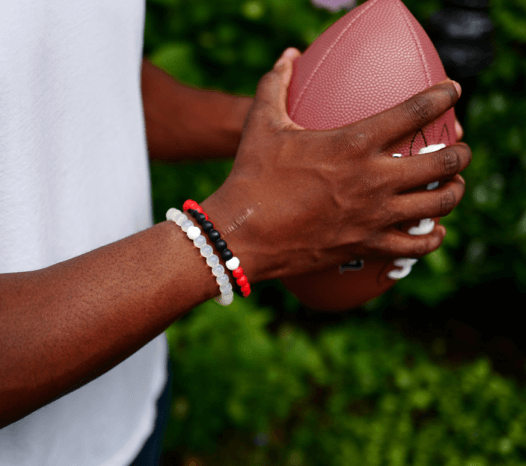 Man holding a football wearing a black and red silicone beaded bracelet.