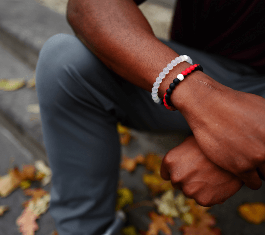 Man holding his wrist wearing a black and red silicone beaded bracelet.