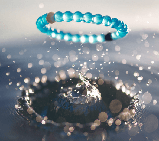 Blue silicone beaded bracelet creating a splash on top of water.