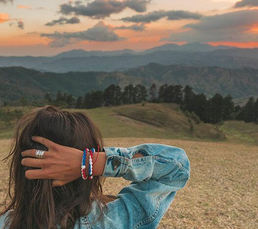Woman wearing red, white and blue swirl silicone beaded bracelet on wrist while touching her hair and looking at mountains.