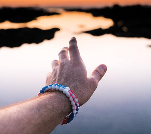 Close up of male wearing red, white and blue swirl silicone beaded bracelet while reaching towards water.