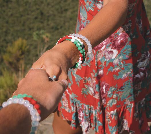 Two girls holding hands and wearing stacks of red, white and green silicone beaded bracelets.