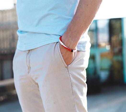 Man wearing red and white swirl silicone beaded bracelet on wrist with hands in his pockets.
