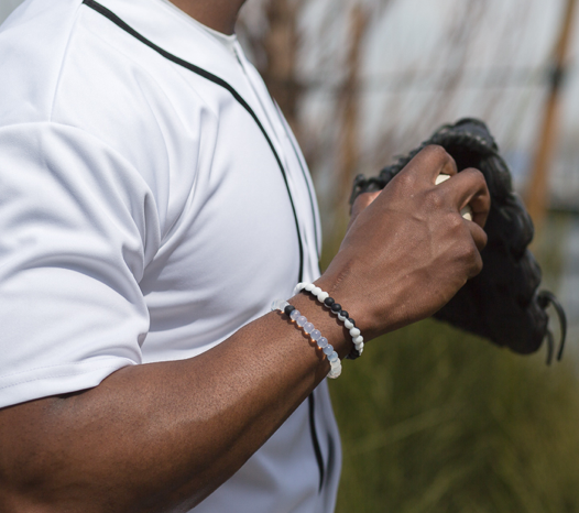 Male wearing black and white silicone beaded bracelet on wrist while holding a baseball.