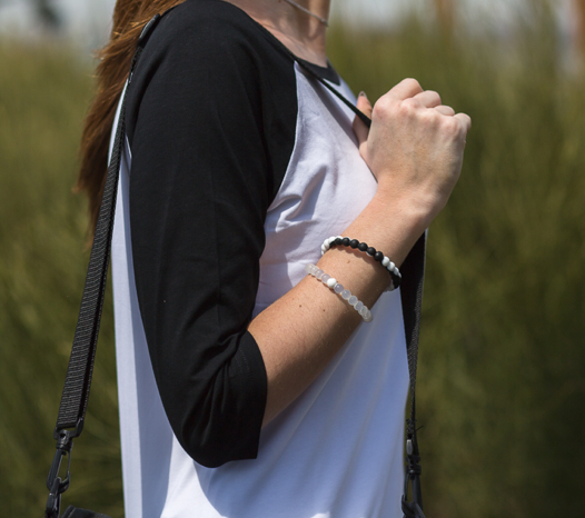 Female wearing black and white silicone beaded bracelet on wrist while holding shoulder bag straps.