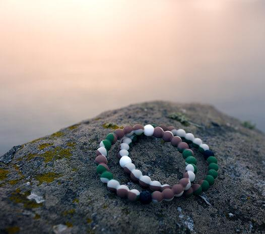 Two cream, brown, and green swirl silicone beaded bracelets sitting on a rock.