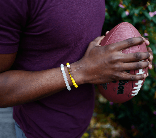 Man holding a football wearing a brown and gold silicone beaded bracelet.