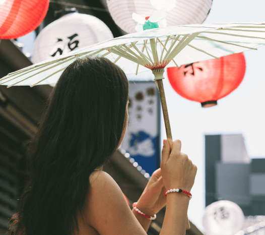 Woman wearing red and white swirl silicone beaded bracelets while holding a white parasol.