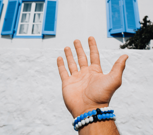 Male hand with two blue and white swirl silicone beaded bracelets on wrist and white house with blue shudders in the background.