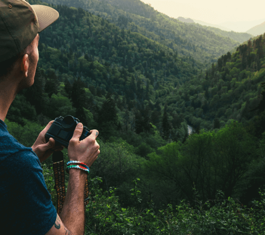 Man holding camera and looking at mountains while wearing red, white and green silicone beaded bracelets.