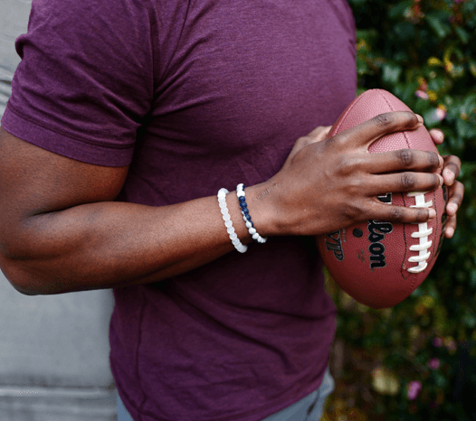 Man holding a football wearing a gray and navy blue silicone beaded bracelet.