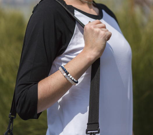 Woman wearing navy blue and white silicone beaded bracelet on wrist while holding shoulder bag strap.