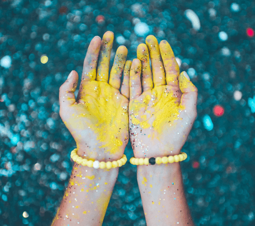 Close up hands covered in glitter and yellow paint with yellow silicone beaded bracelets on wrist.