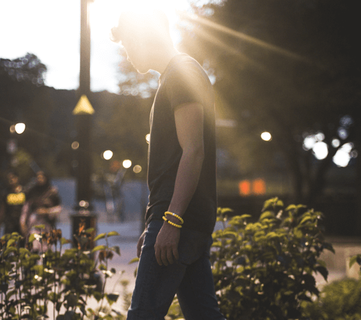 Male wearing two yellow silicone beaded bracelets on wrist with sun shining behind his head.