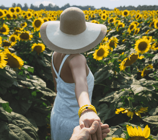 Woman walking in sunflower field wearing two yellow silicone beaded bracelets on wrist.