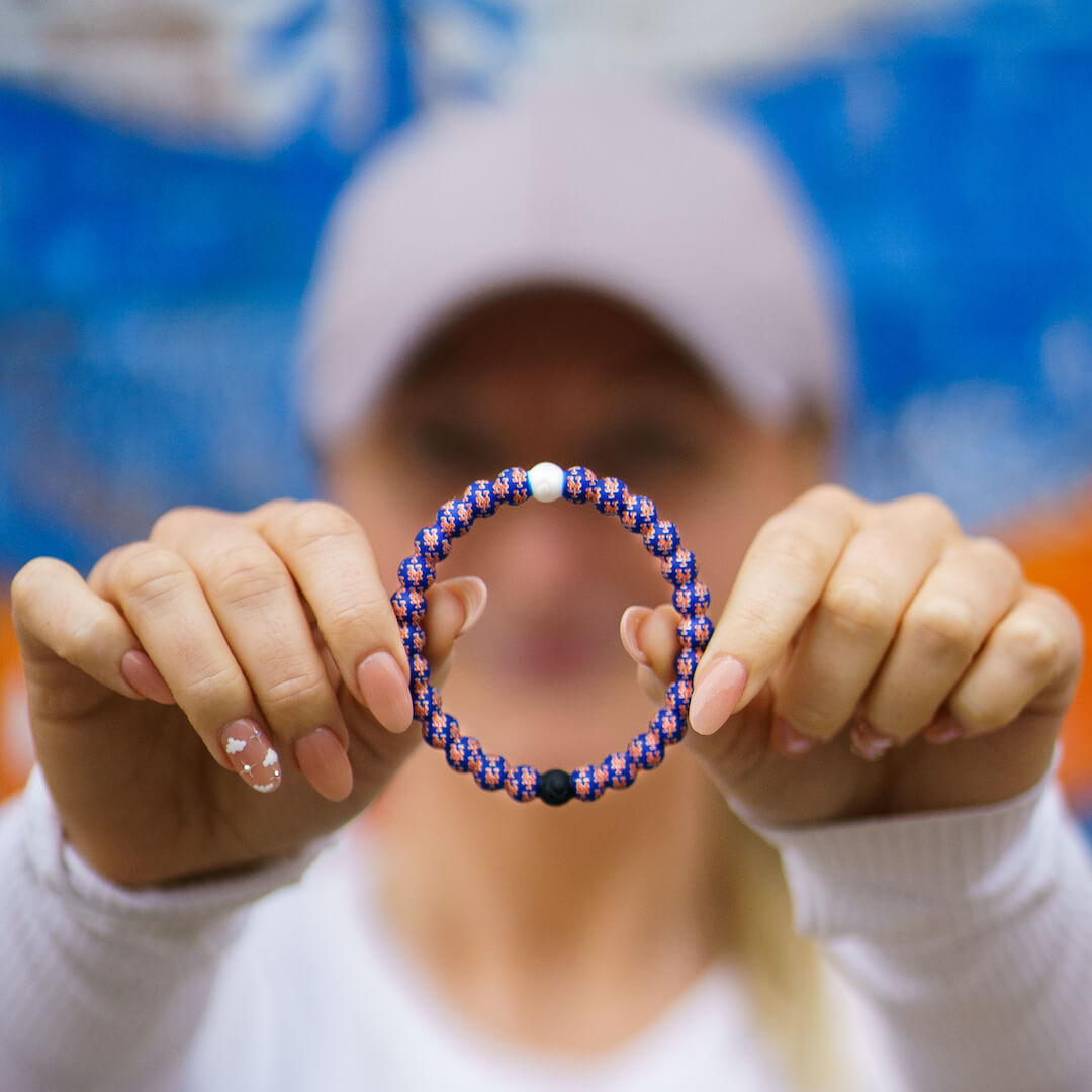 Woman holding a silicone beaded bracelet with New York Mets logo pattern.