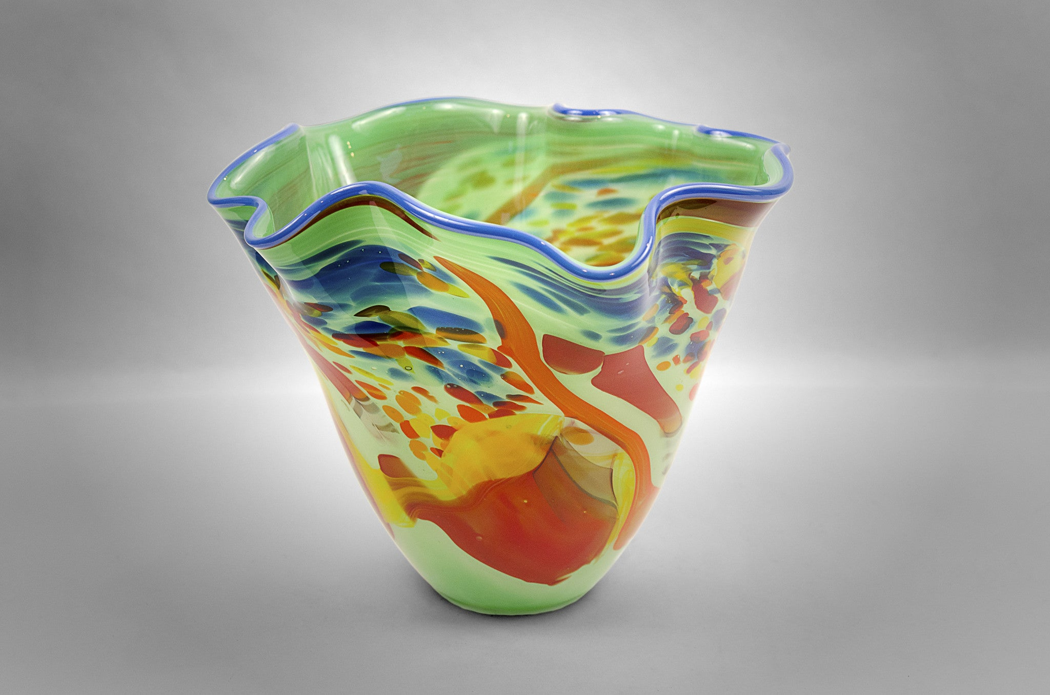 Fluted bowl / vase with broken shards of recycled glass and light green base color and blue rim