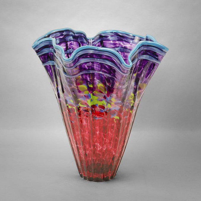 Fluted kaleidoscope vase with ruby and purple colors and blue rim