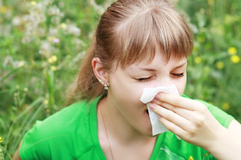 women blowing nose in green field