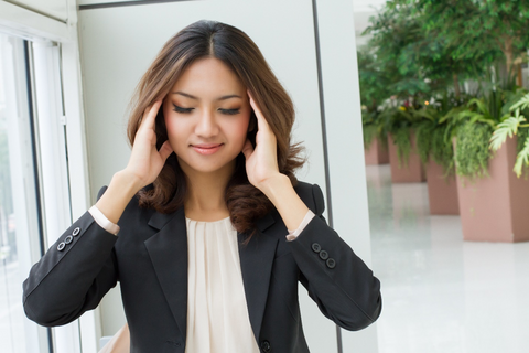 women relieving pressure on head
