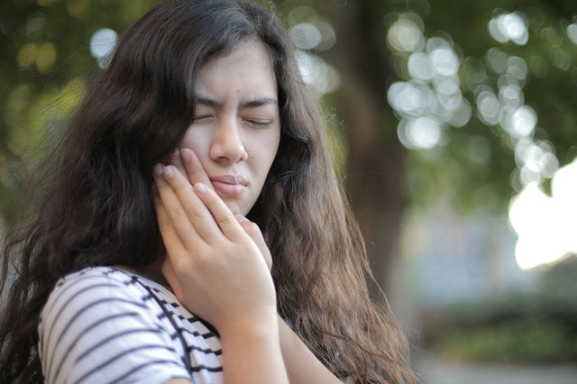 Woman dealing with toothache symptoms due to swollen gums