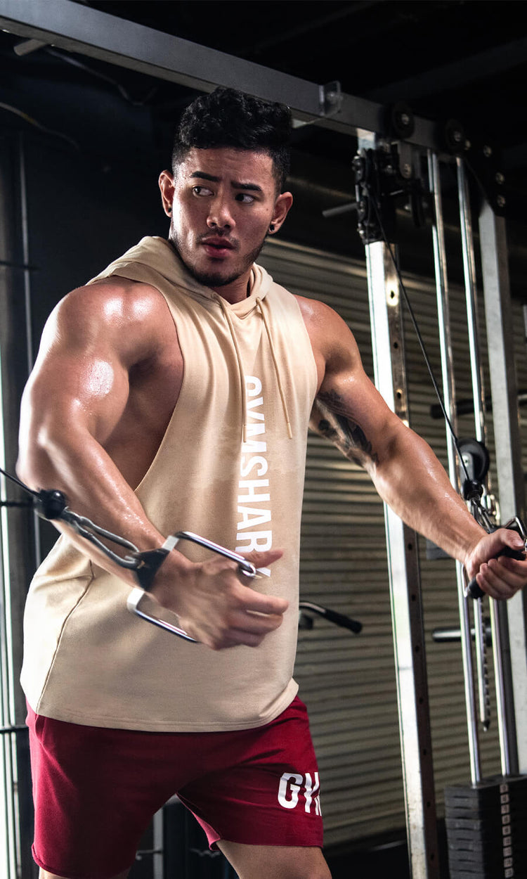Gymshark athlete in a low light iron gym flexing on the cable machine. Maximize clothing standing out in a dark environment.