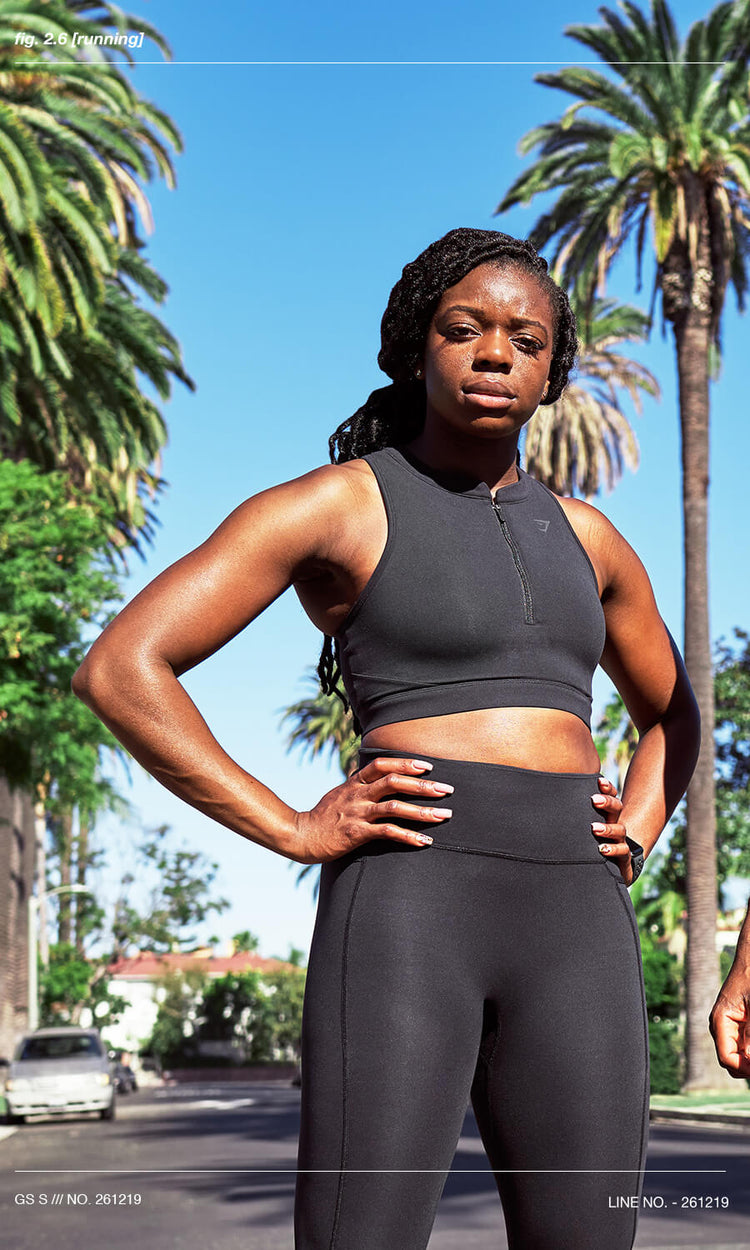A women wearing the Gymshark Speed collection posing with her hands on her hips after completing a run.