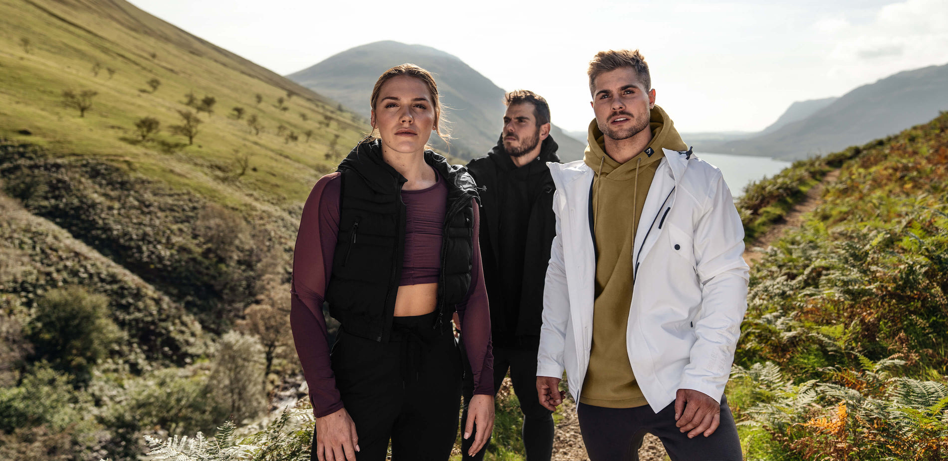 : Three Gymshark athletes modelling outerwear in front of a scenic back drop of Lake District. The banner also demonstrates men's and women's layered clothing for cold environment.