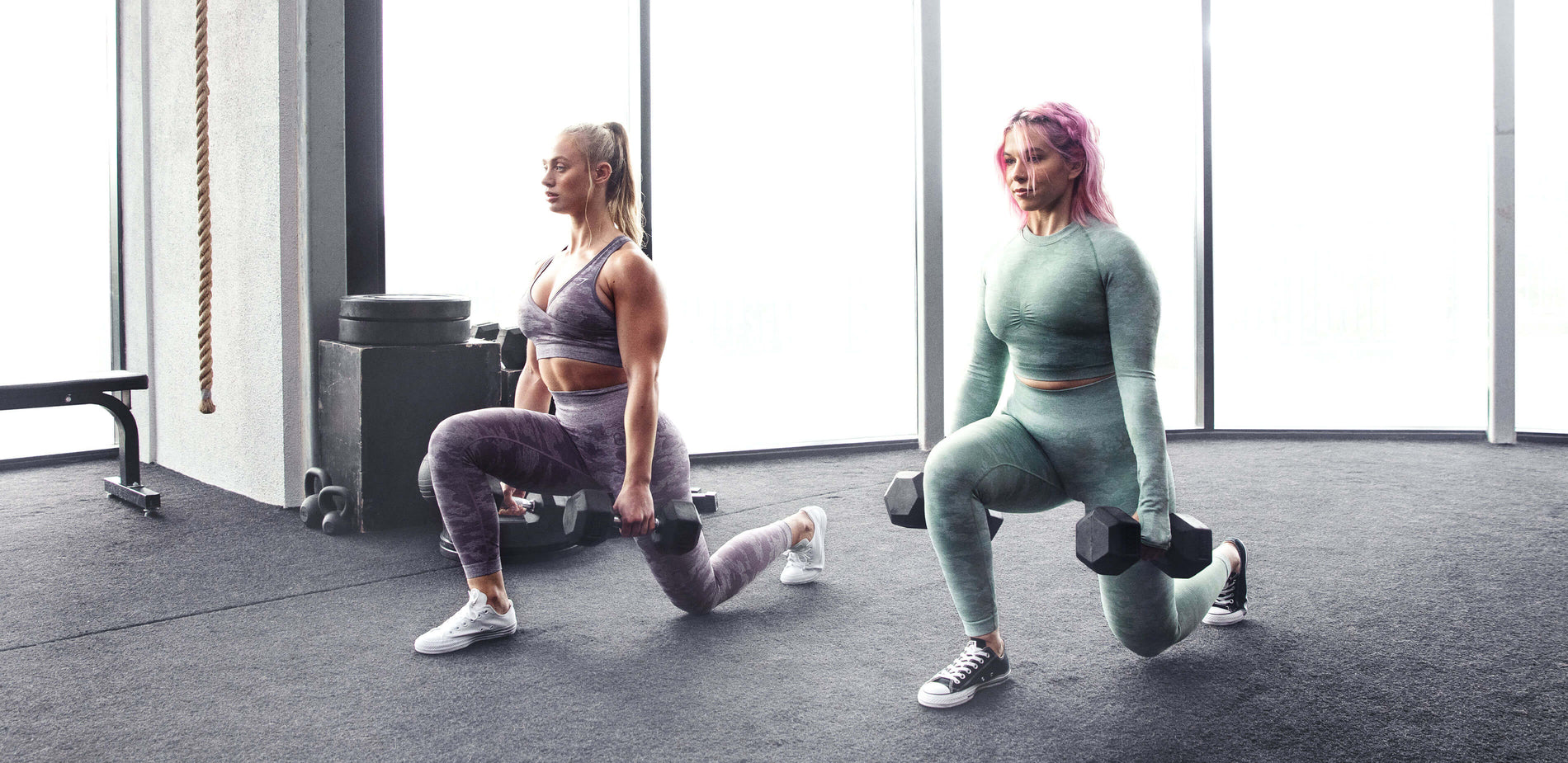 Two female Gymshark athletes lunging in a bright naturally lit gym wearing the new Camo collection.