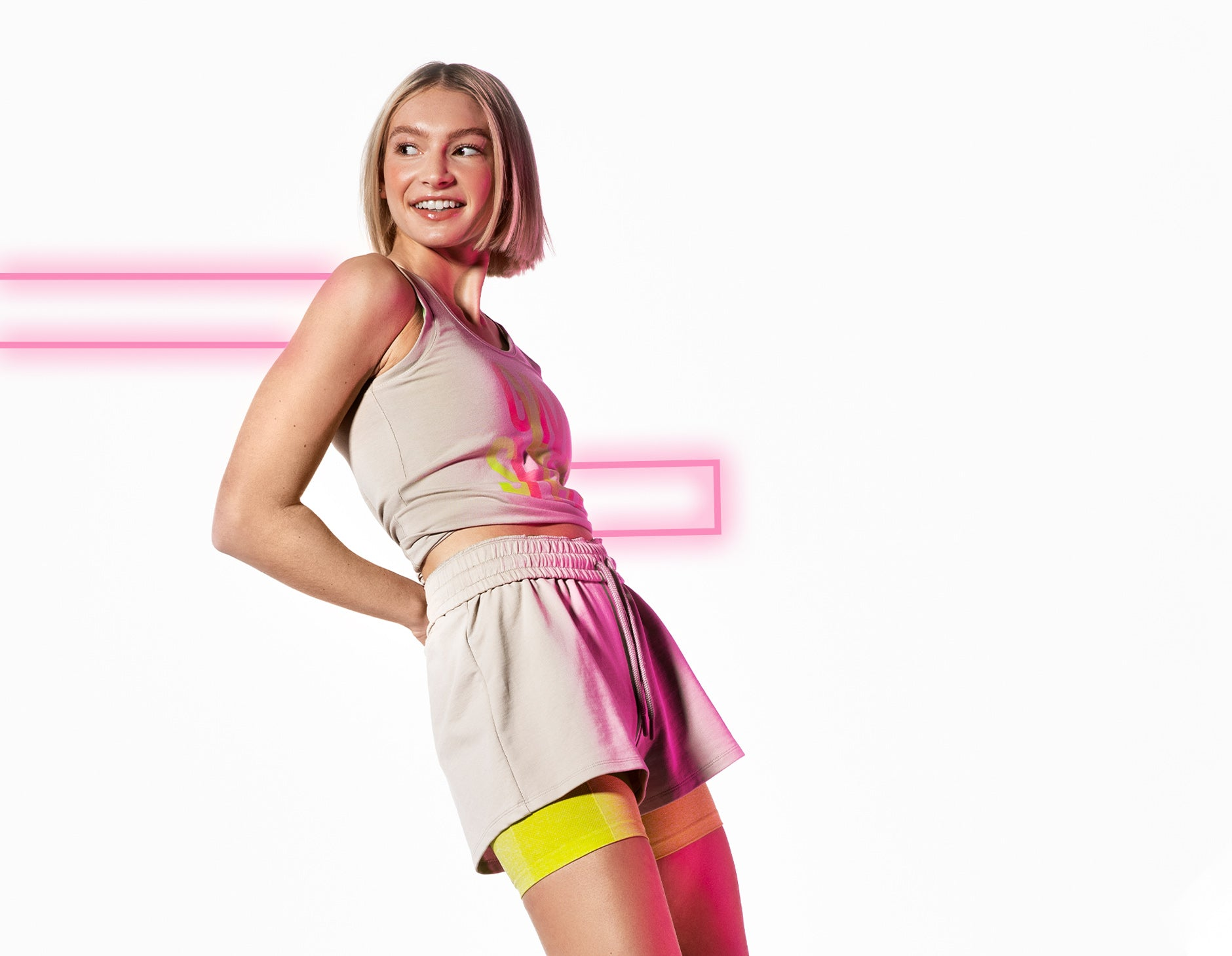 Female Posing while wearing the Strobe Vest in grey with neon pink graphics on the background.
