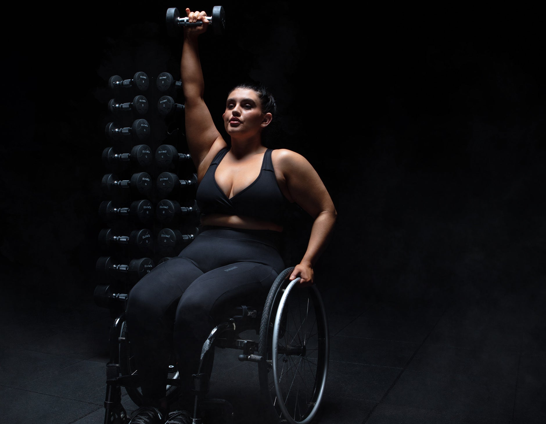 Sophie Butler lifting weights while wearing the Chalk collection in a black room with a spotlight on her.