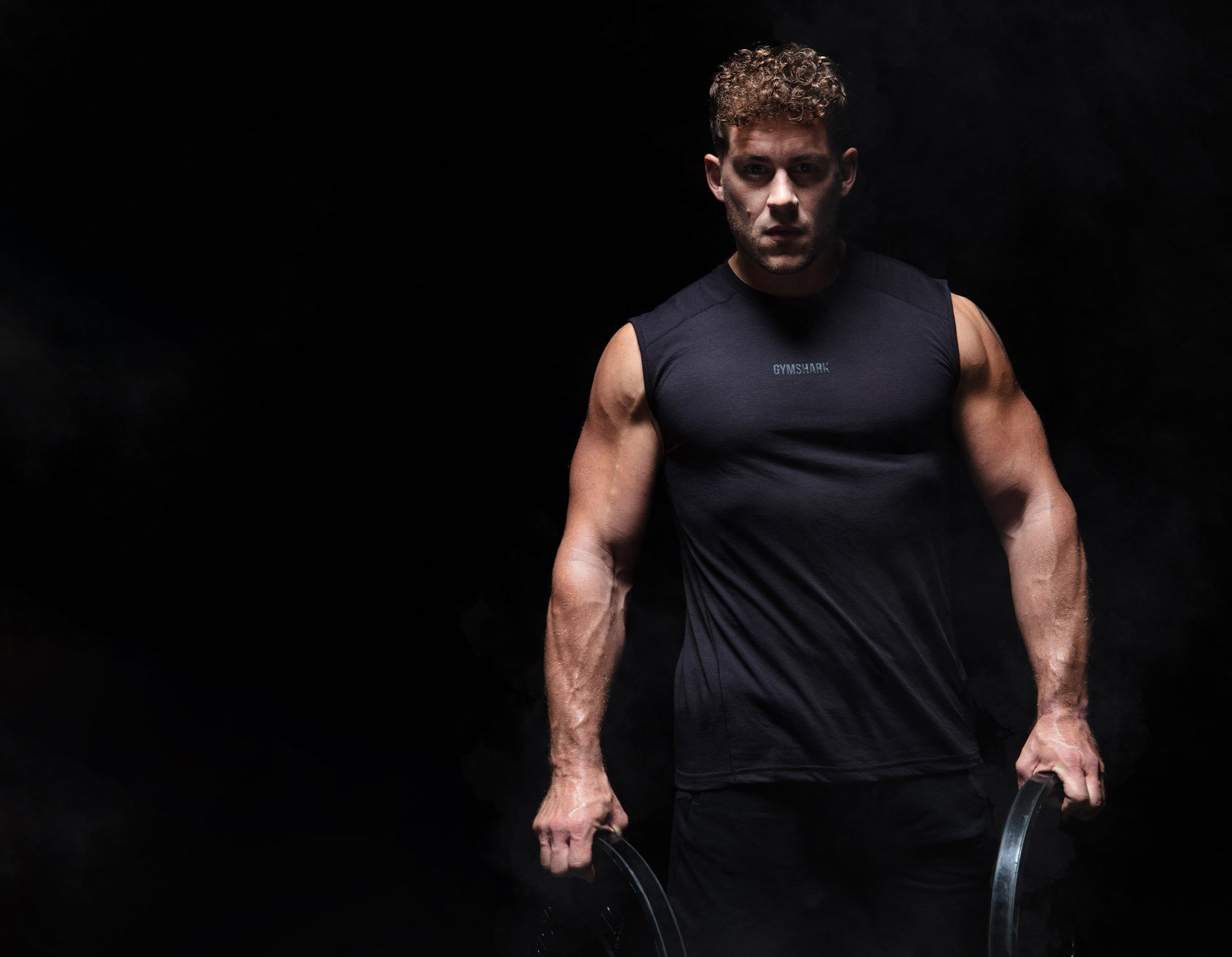 Jack Eyers lifting weights while wearing the Chalk Collection in a black room with a spotlight on him.
