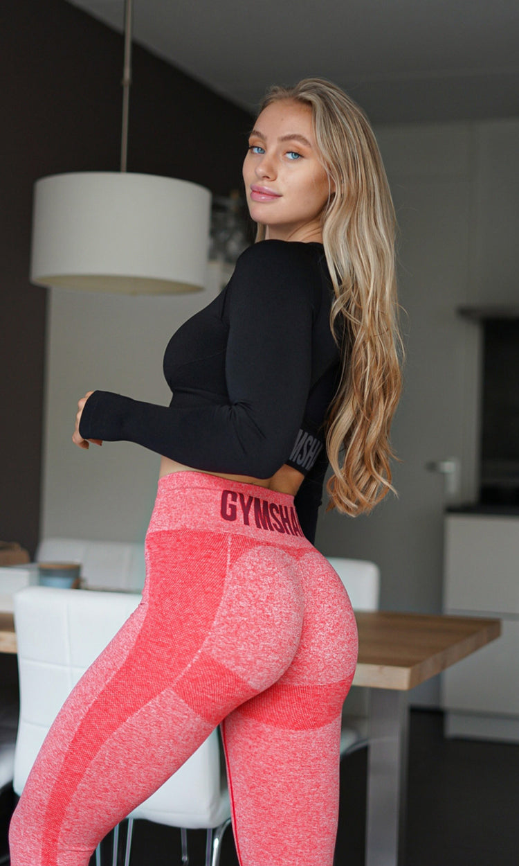 Guujse wearing the Flex leggings in Red and crop top in black in her kitchen.