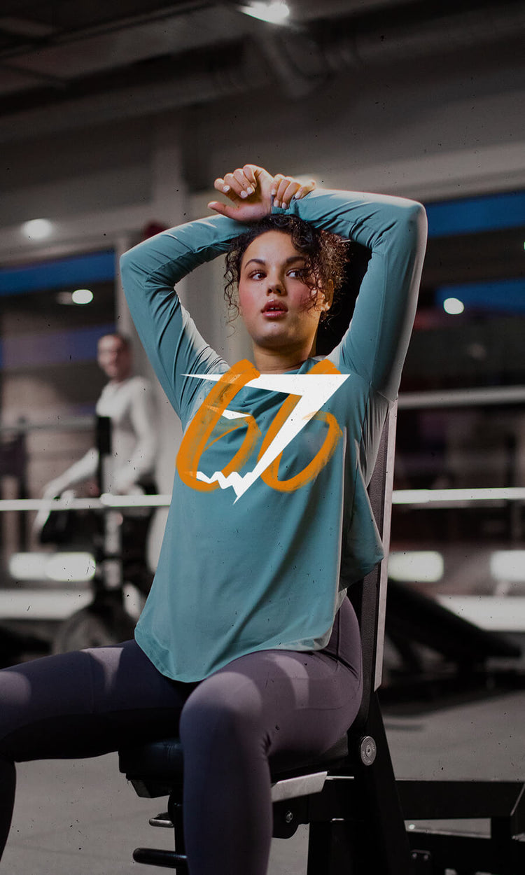 Women on a workout bench resting between sets with hands above her head with the Gymshark66 Logo in centre of image.