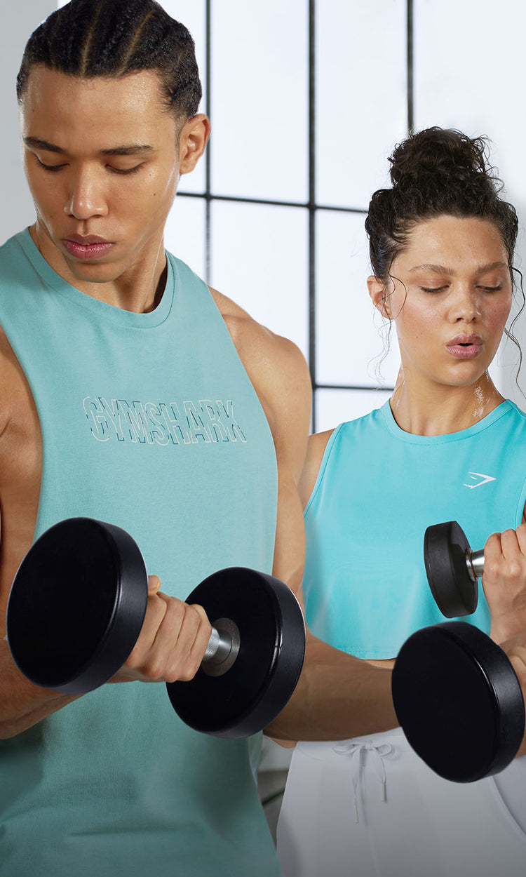Female wearing new Training and male wearing new Outline while doing a home workout in a bright room with big windows.