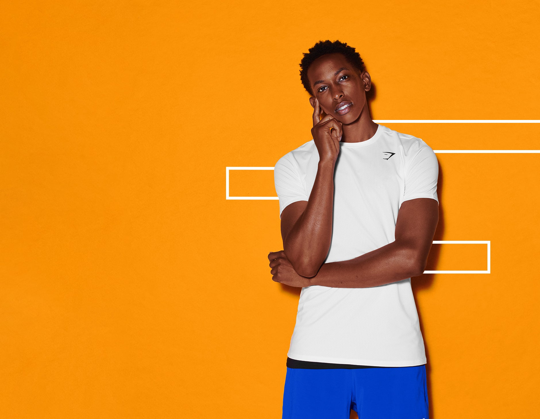 Male posing in a white Arrival t-shirt against an orange background with white graphics.